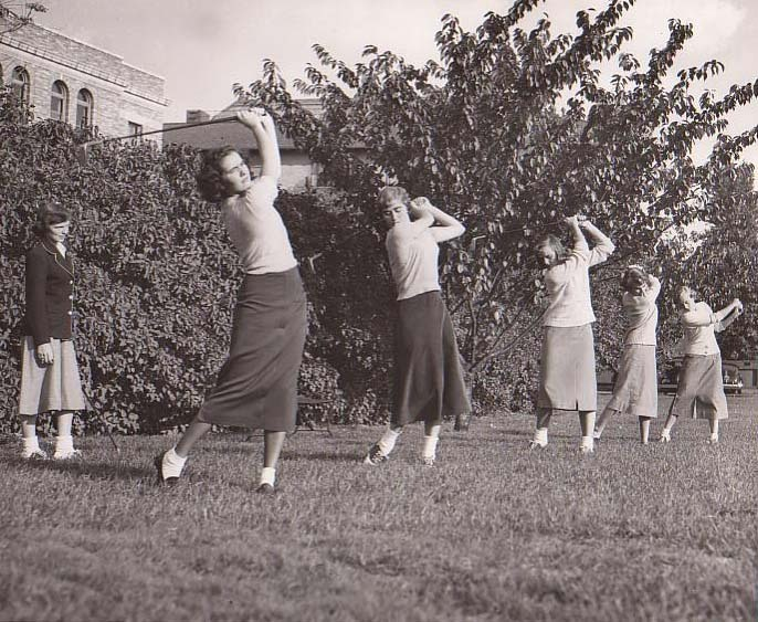 Students practice golf swing on field behind Main College Building (1949)